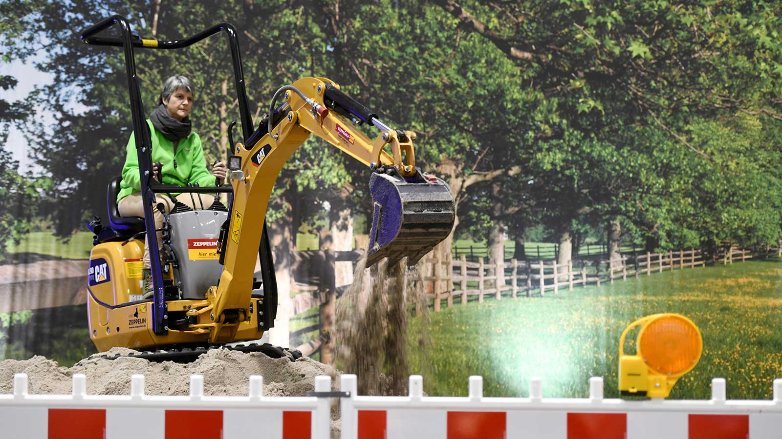 A female visitor on an excavator at the Messer home2 trade show in the Hamburg exhibition halls