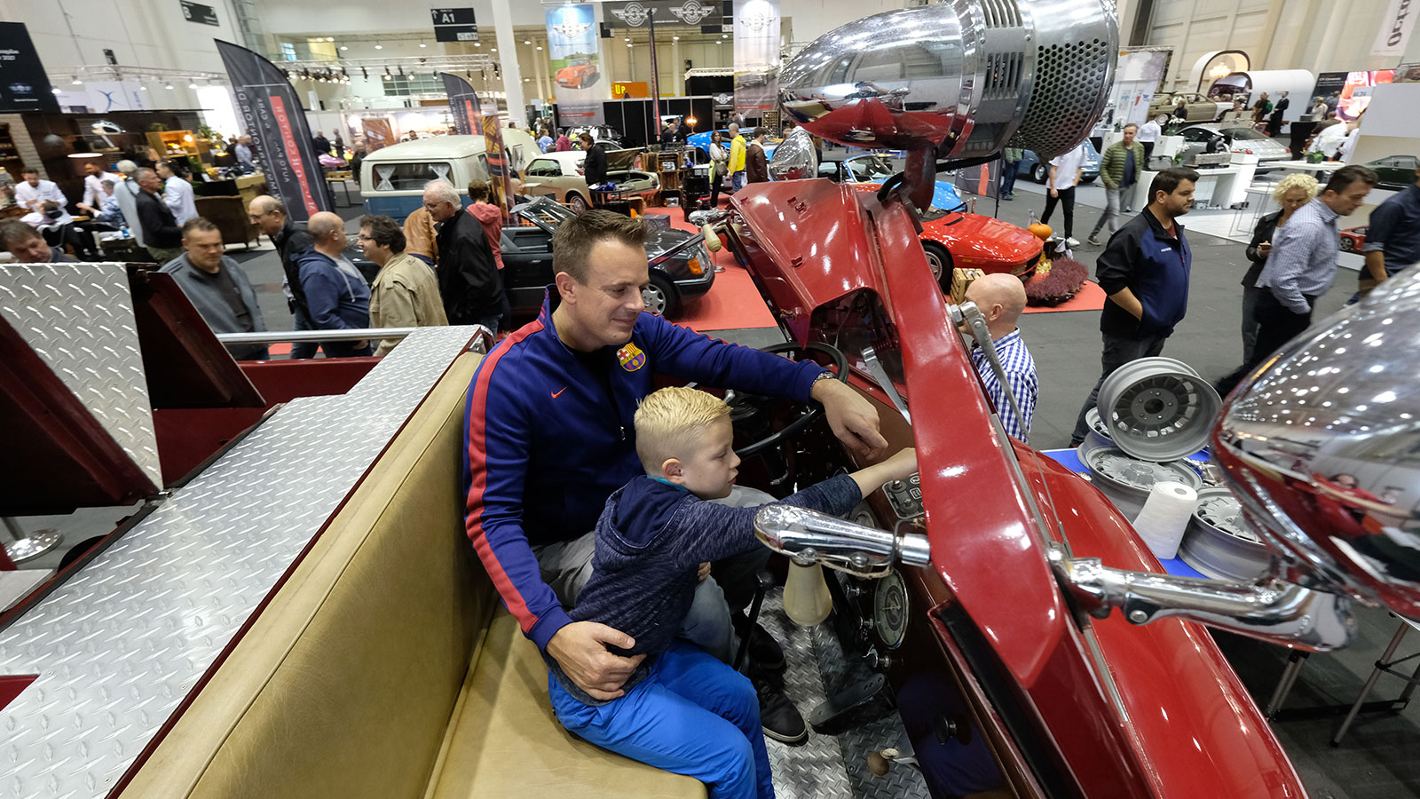 Hamburg Motor Classics: a child and an adult visitor in a classic car