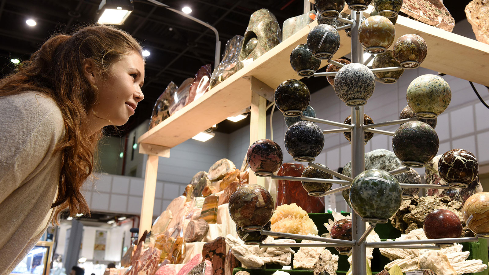 A female visitor standing in front of minerals at the Mineralien Hamburg trade show in the Hamburg exhibition halls
